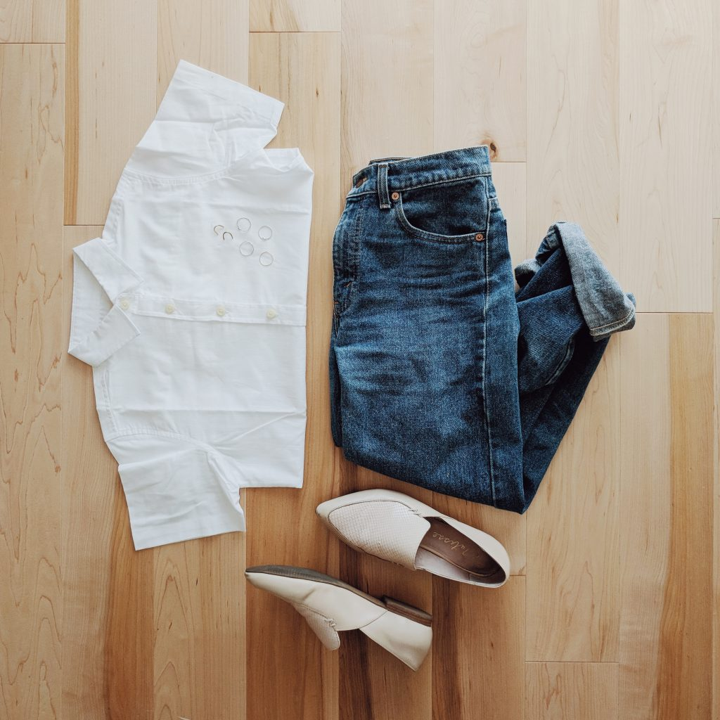 Tradlands Lily White Button-Up laying flat on a wood floor with beige loafers and vintage blue jeans