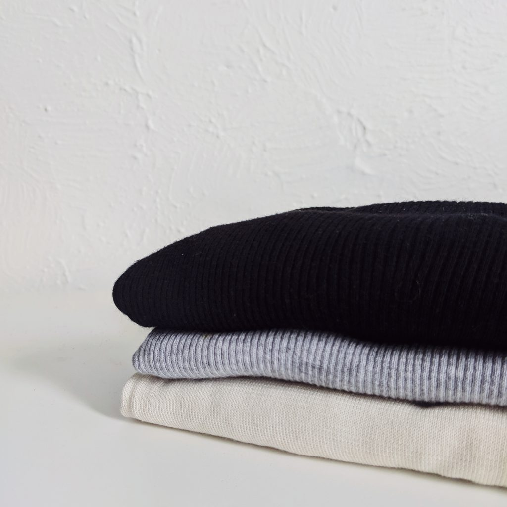 Three sweaters, one black, one grey, one ivory, folded on a white shelf