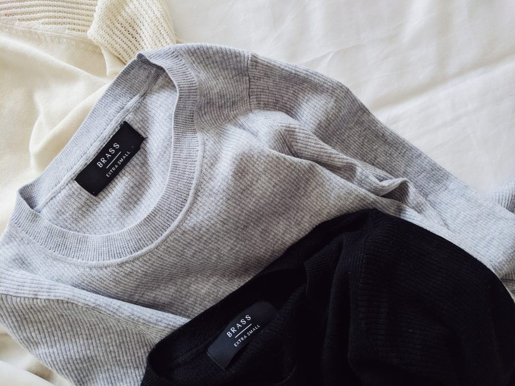 Three sweaters, one ivory, one grey, one black lying on a white comforter