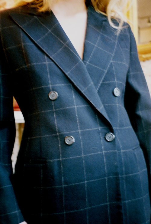 Close-up of a woman's torso, wearing a black wool Ralph Lauren vintage blazer with white windowpane pattern and double-breasted buttons.