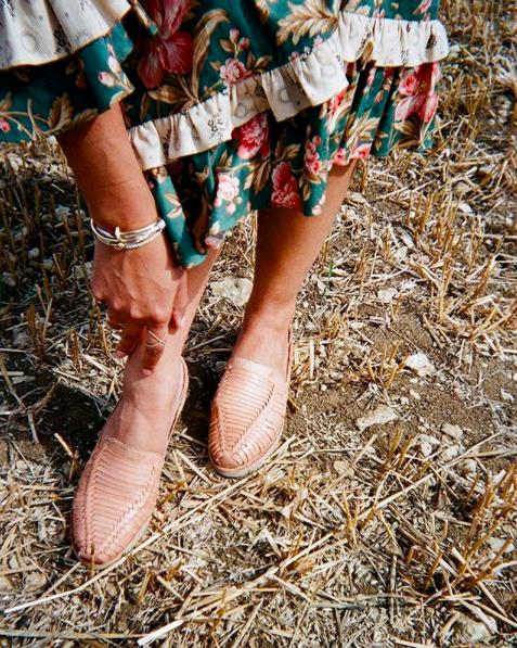 Close-up of a woman's feet, wearing woven huarache shoes.