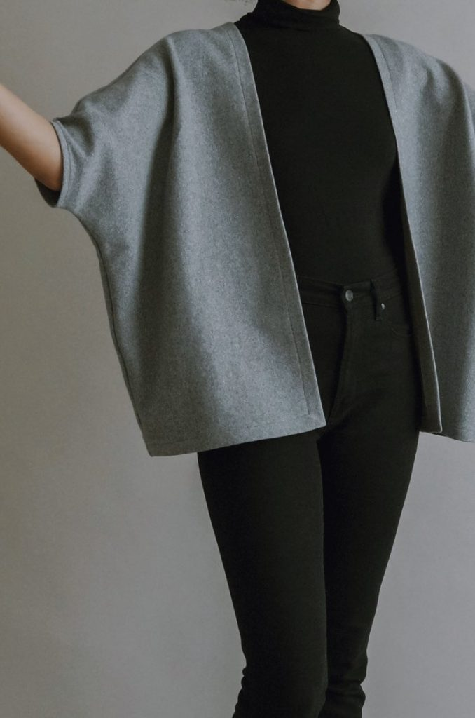 Close-up of woman's torso, wearing a black turtleneck and boxy, structured grey cardigan with batwing sleeves to the elbow.