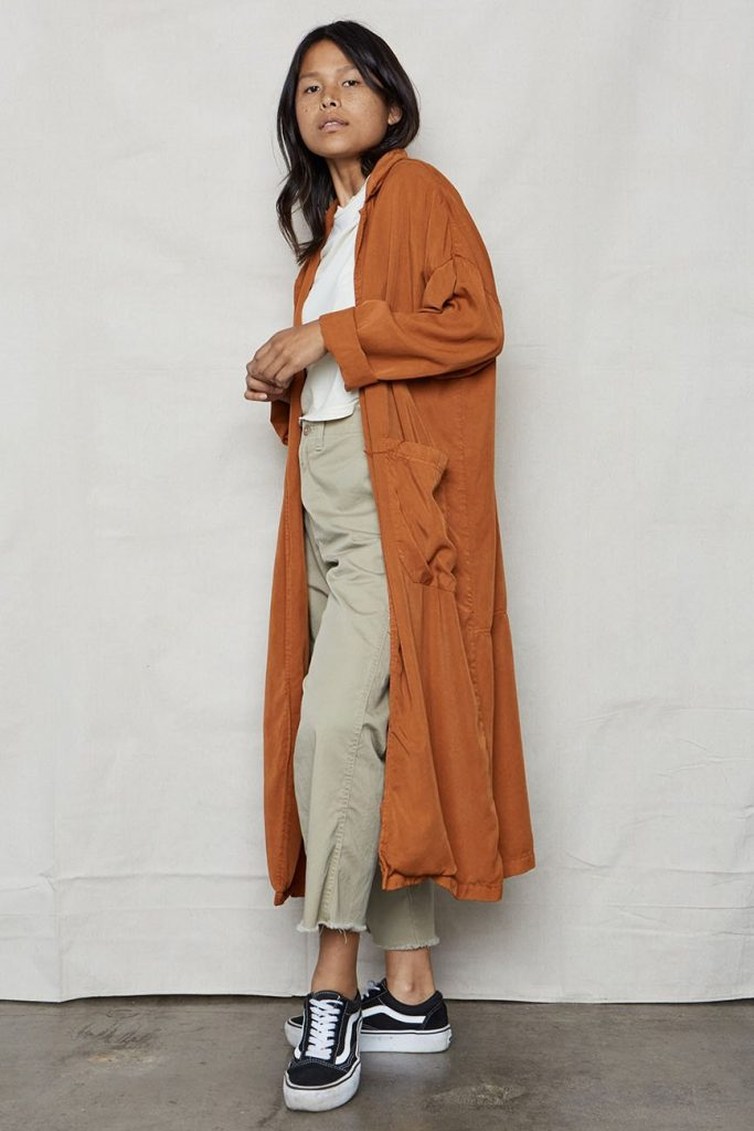 Full-body shot of a woman standing on a white background, wearing a long orange robe, white t-shirt and neutral pants.