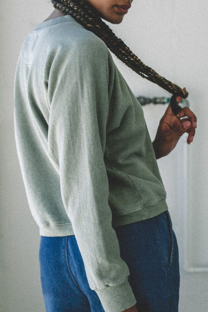 Close-up of a woman's torso, turned away from camera and looking over her shoulder. She's wearing a sage green pullover sweatshirt.