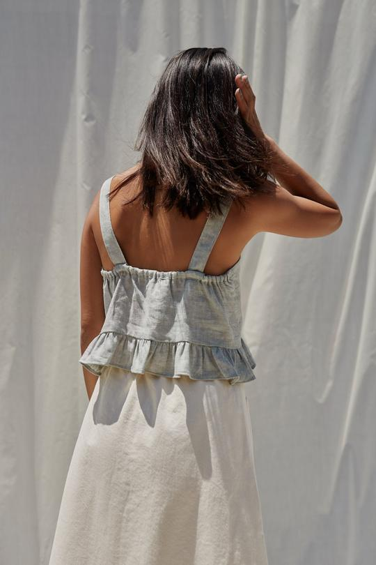 Woman with her back turned, wearing a sage green peplum tank top of linen.