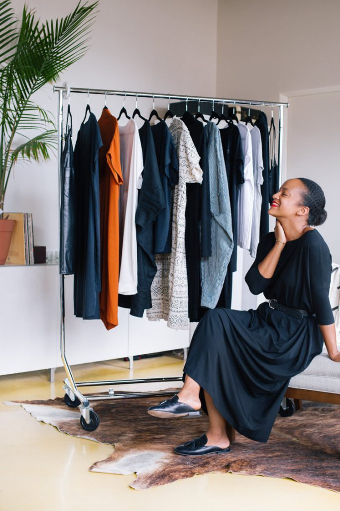 Nat, the founder of Tiny Closet, sitting on an upholstered bench in front of a clothing rack inside a minimalist room and looking up joyfully.