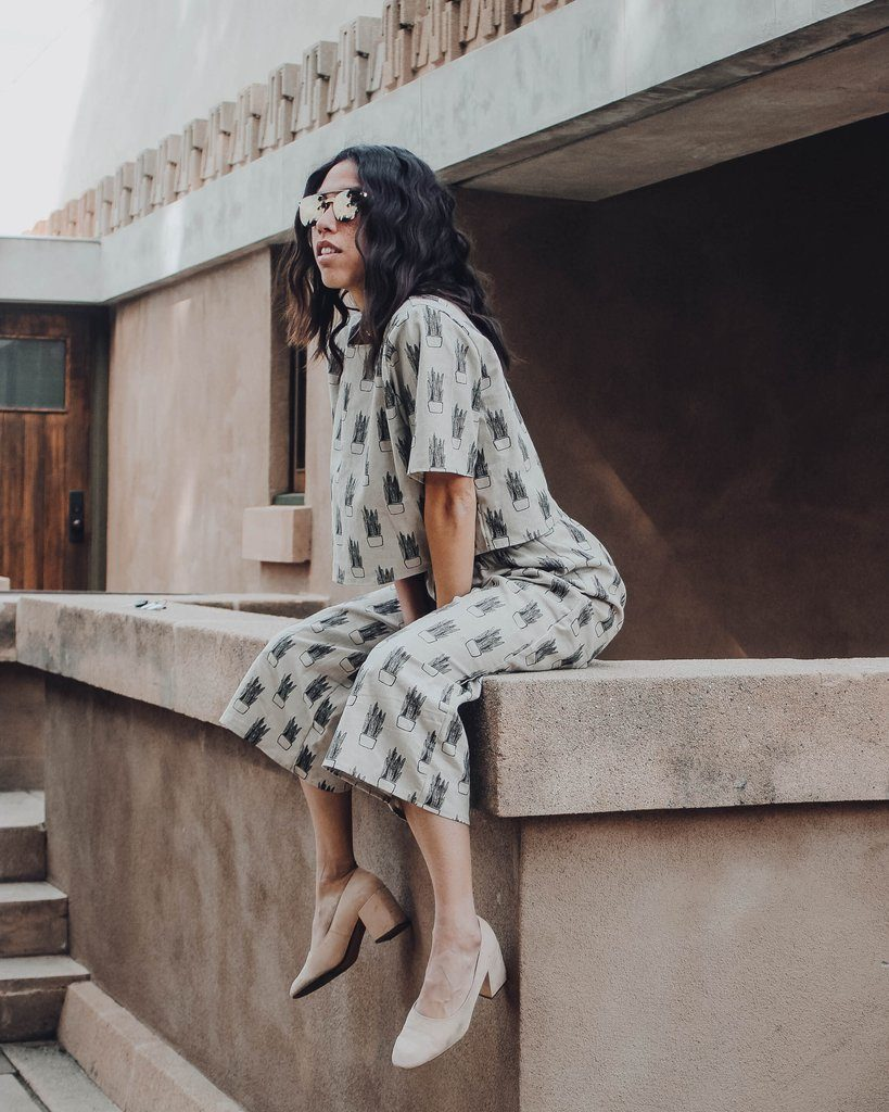 Woman sitting on a concrete wall wearing aviator sunglasses, and matching linen top & culotte pants that are printed with a pattern of snake plants.