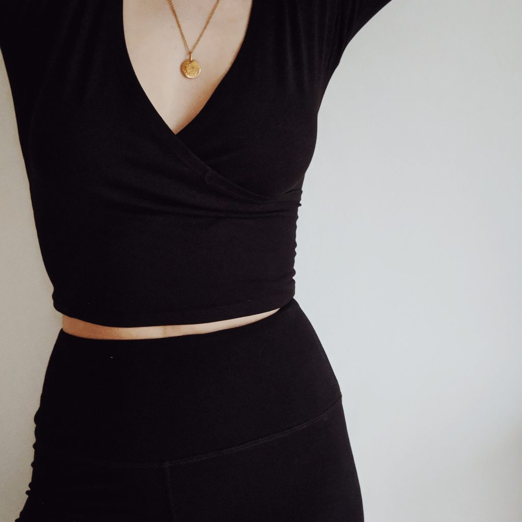 Abdomen of a woman wearing black high waisted leggings and a black wrap top