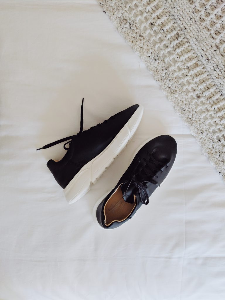 Black and white sneakers lying sideways on a white blanket