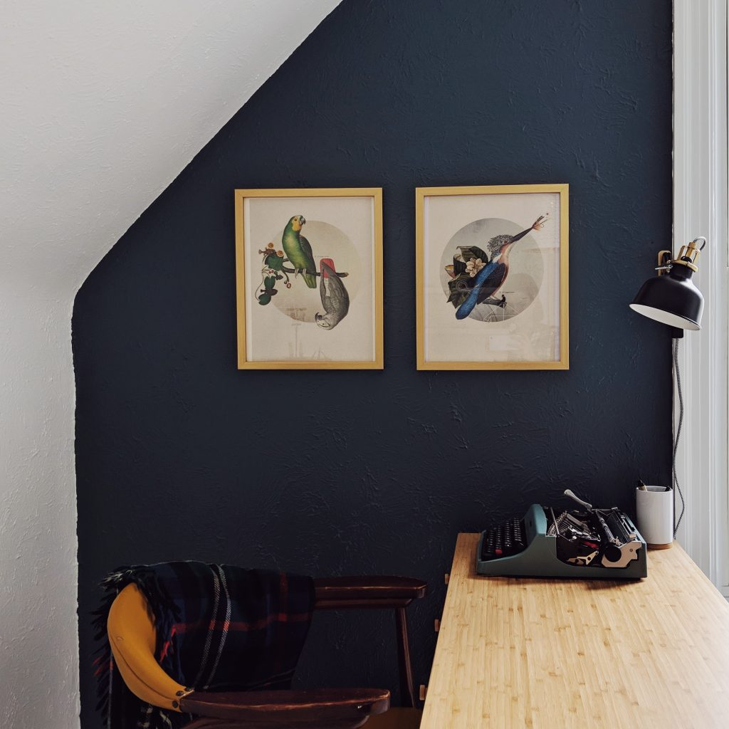 Home office painted white with a navy blue accent wall