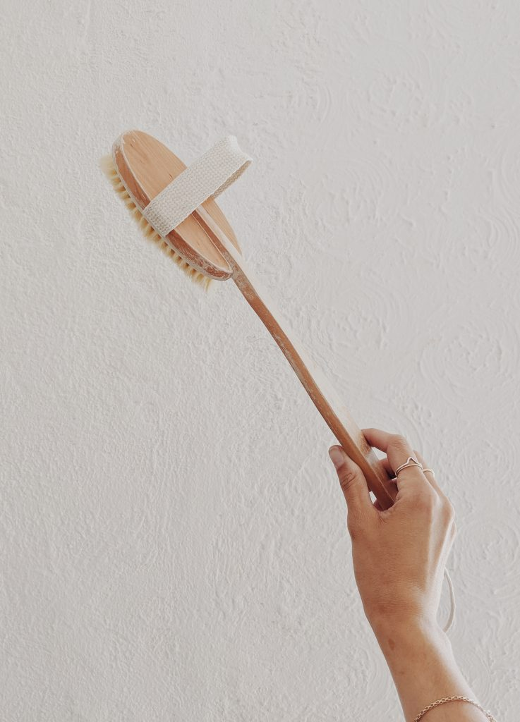 A wooden body scrubber brush held by a hand against a white wall