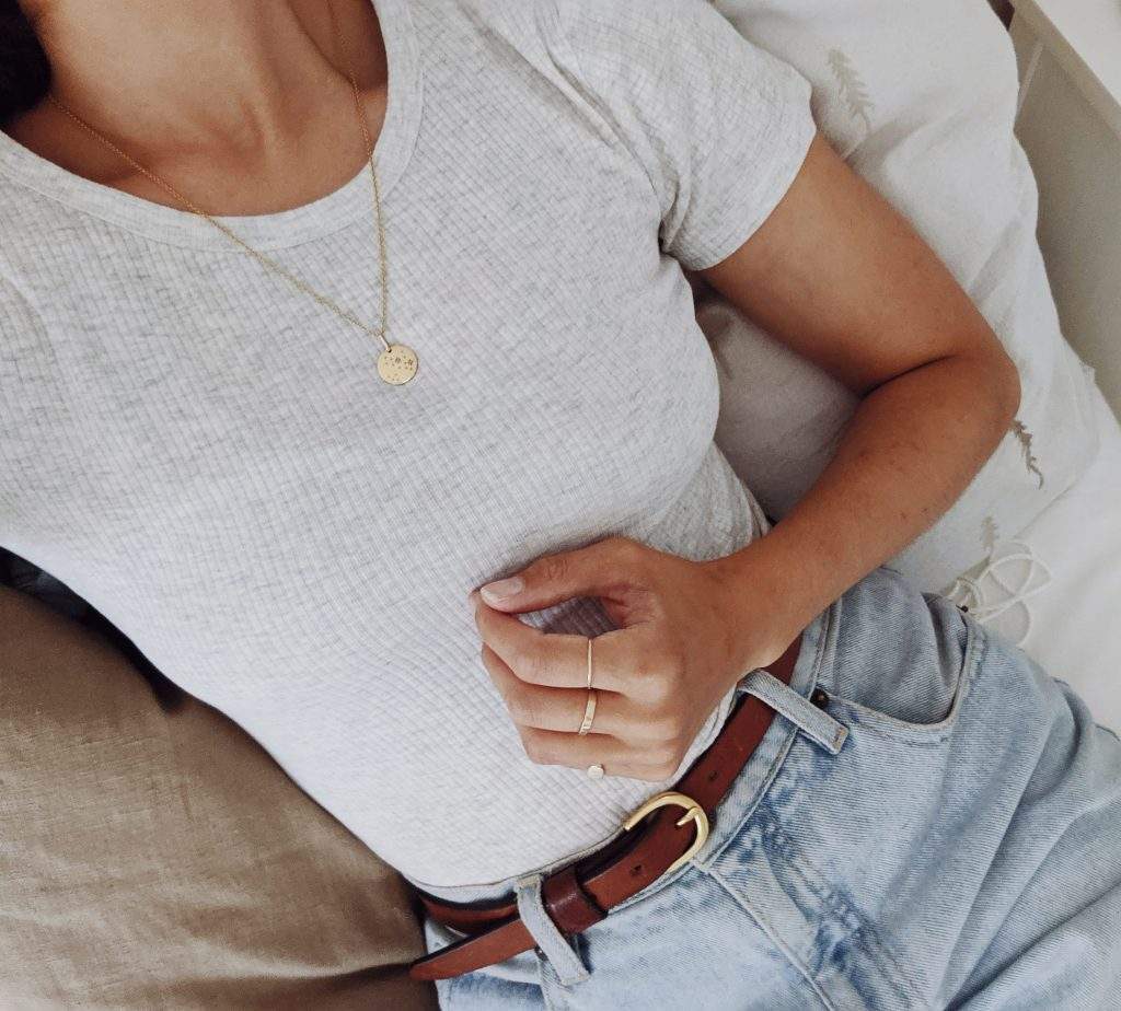 Woman's torso, sitting on a bed and wearing a plain t-shirt with gold rings and necklace