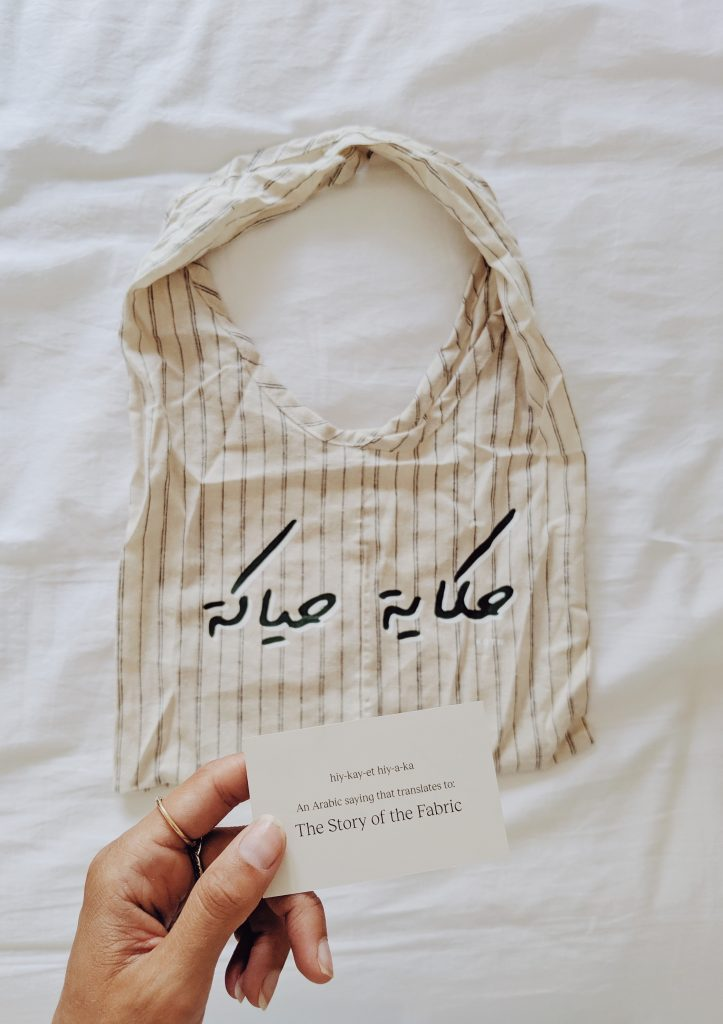 "A fabric bag with an Arabic phrase, lying on a bed. A hand holding a card saying ""The Story of the Fabric"" translates the Arabic phrase"