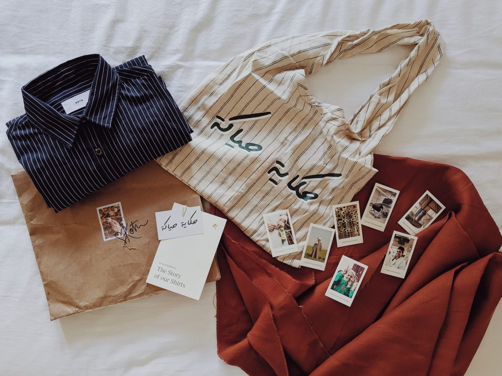 An assortment of clothes, a woven bag, and rust coloured fabric lying on a bed