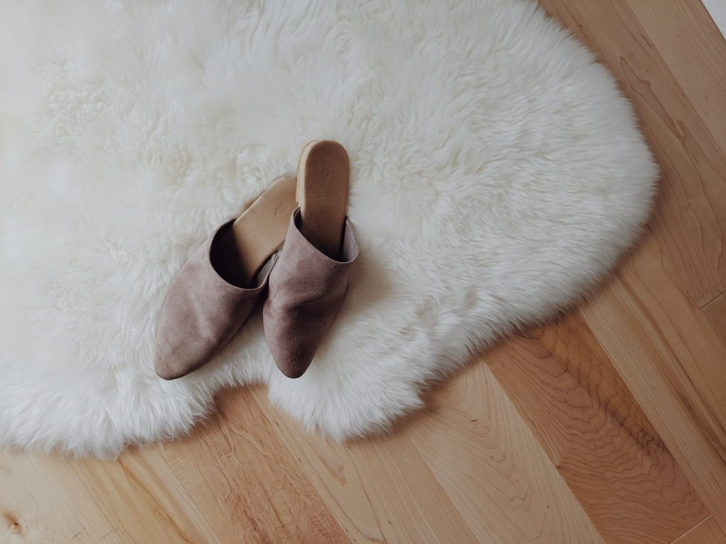 Taupe pointed toe suede slides on a sheepskin rug