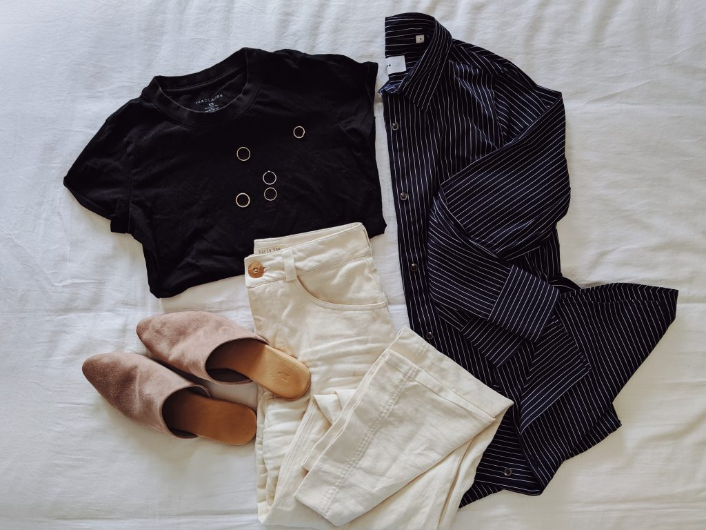 Kotn's navy pinstripe shirt dress folded on a bed styled with white wide leg pants, a black t-shirt and taupe slide shoes
