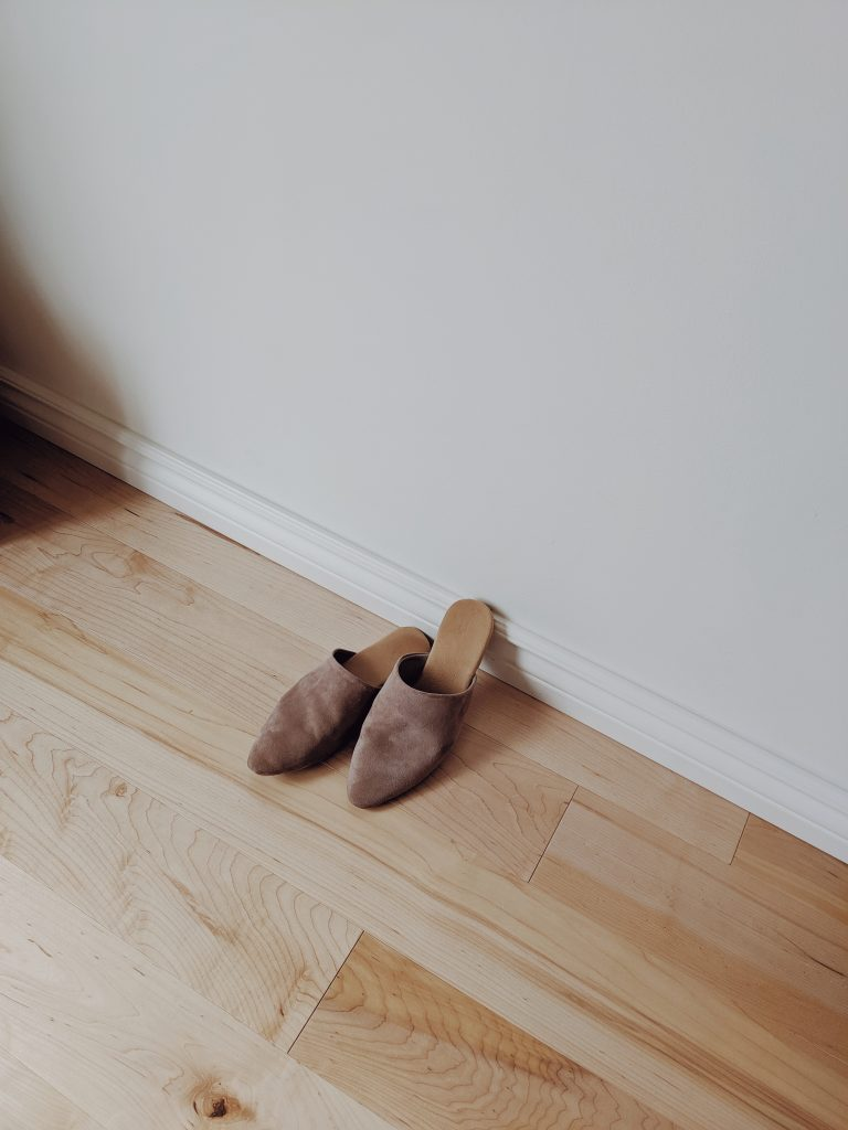taupe suede pointed toe slides on a natural maple hardwood floor