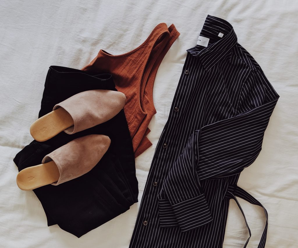 A pinstriped blouse, rust coloured tank top and taupe suede slides