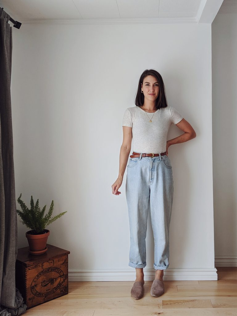 A woman with shoulder length brown hair standing against a white wall wearing a fitted oatmeal tee, belted mom jeans and taupe slide shoes