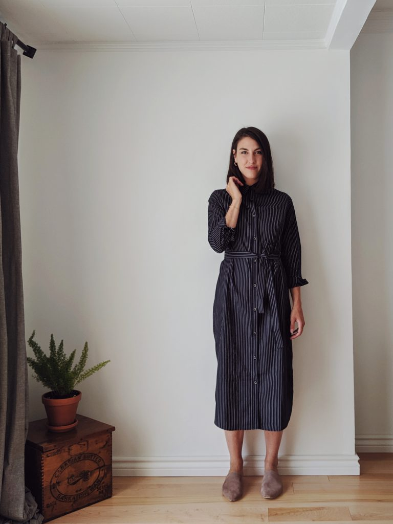 Woman with shoulder length brown hair standing against a white wall wearing a midi length shirt dress that is navy with thin pinstripes, and a pair of taupe slide shoes