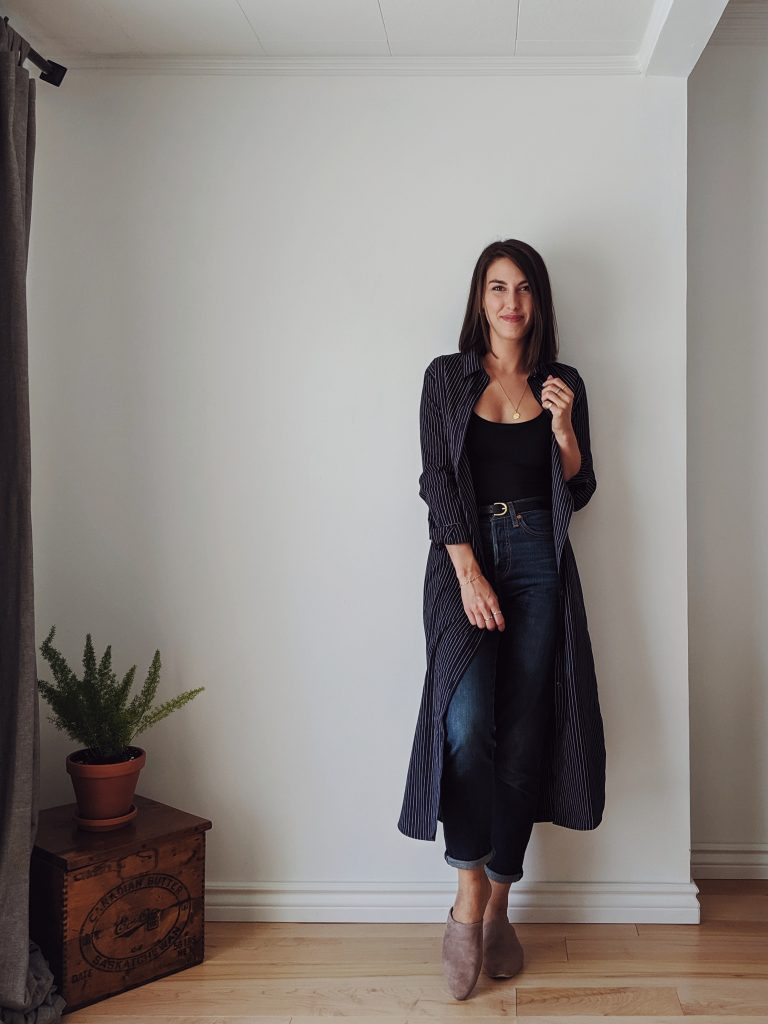 Woman with shoulder length brown hair standing against a white wall wearing a midi length shirt dress that is navy with thin pinstripes, worn open like a long cardigan paired with dark skinny jeans and a black tank top