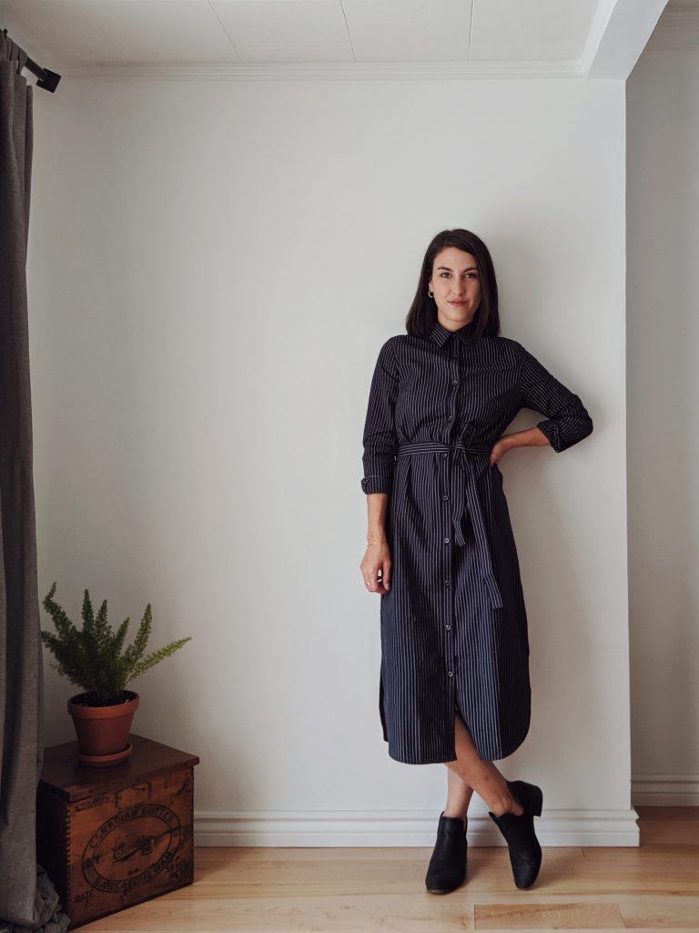 Woman with shoulder length brown hair standing against a white wall wearing a midi length shirt dress that is navy with thin pinstripes, and a pair of black booties