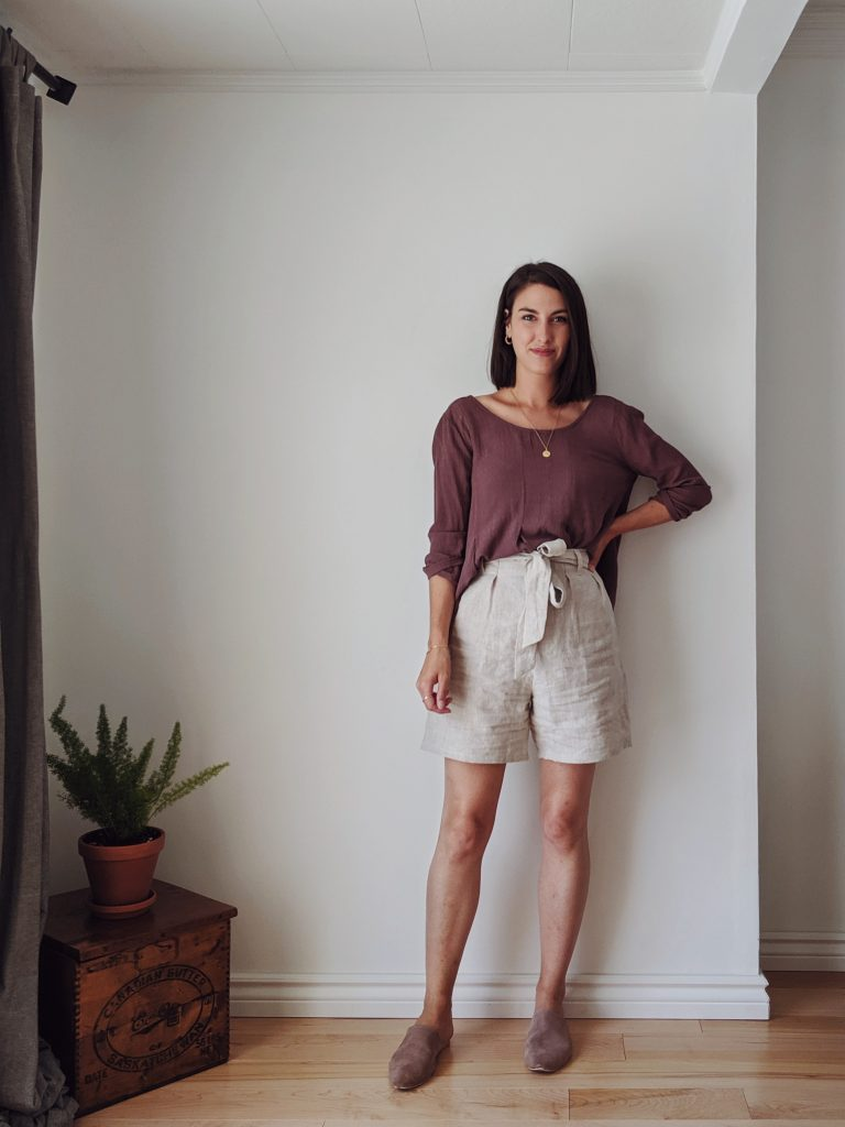 A woman with shoulder length brown hair standing against a white wall and wearing the taupe slides with beige linen shorts and a relaxed mauve top