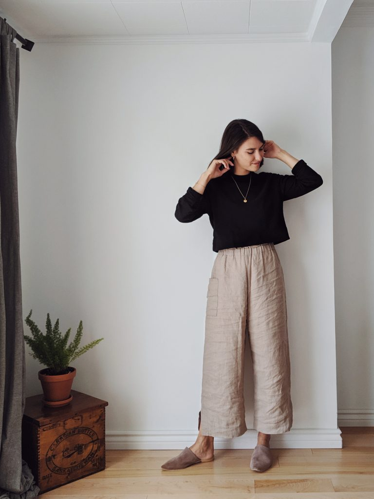 A woman with shoulder length brown hair standing against a white wall wearing a cropped black sweatshirt and wide legged sand coloured linen trousers