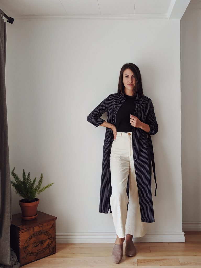 Woman with shoulder length brown hair standing against a white wall wearing a midi length shirt dress that is navy with thin pinstripes, worn open like a long cardigan paired with white wide leg trousers and a black t-shirt