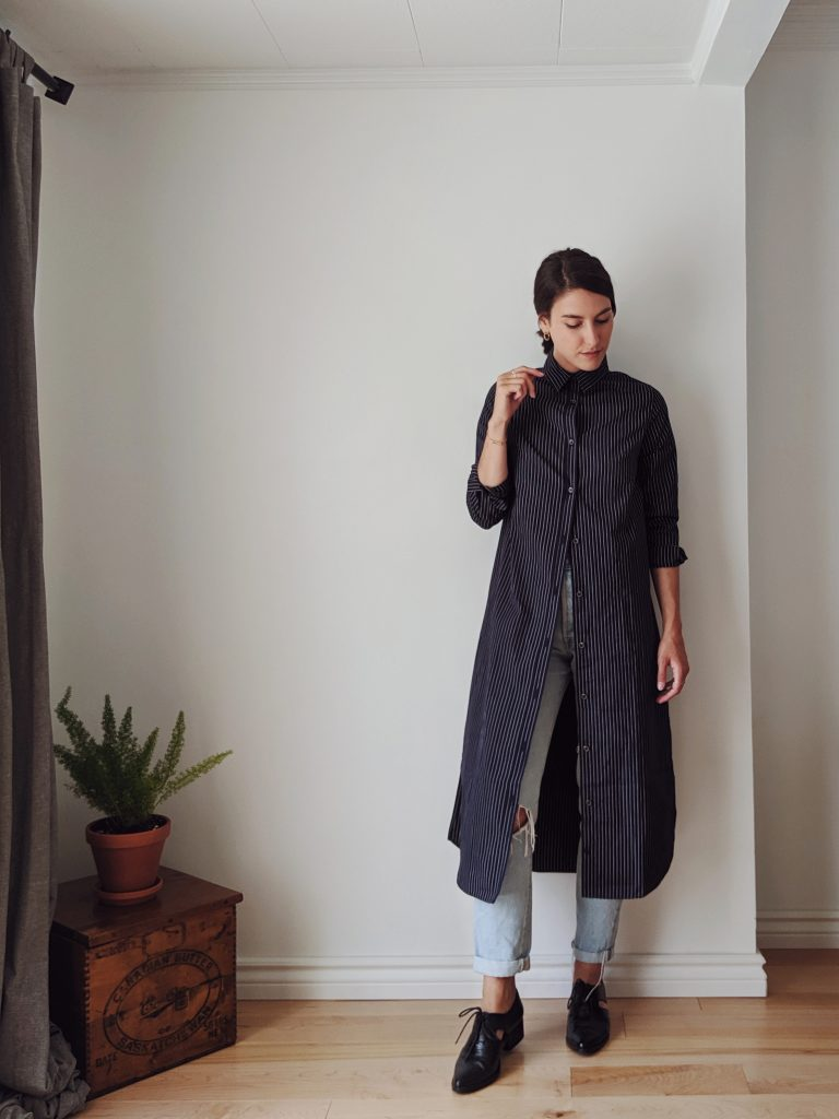 Woman with shoulder length brown hair standing against a white wall wearing a midi length shirt dress over a pair of light jeans, with black booties
