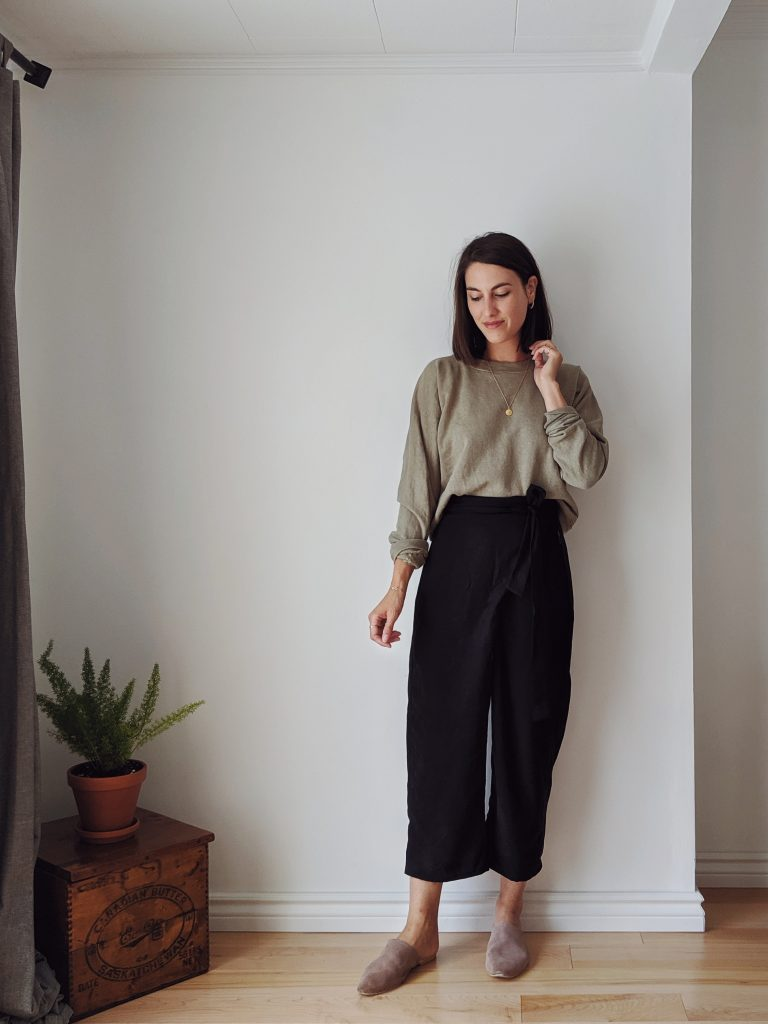 A woman with shoulder length brown hair standing against a white wall wearing a sage-coloured sweatshirt and black wrap pants with casual taupe slide shoes