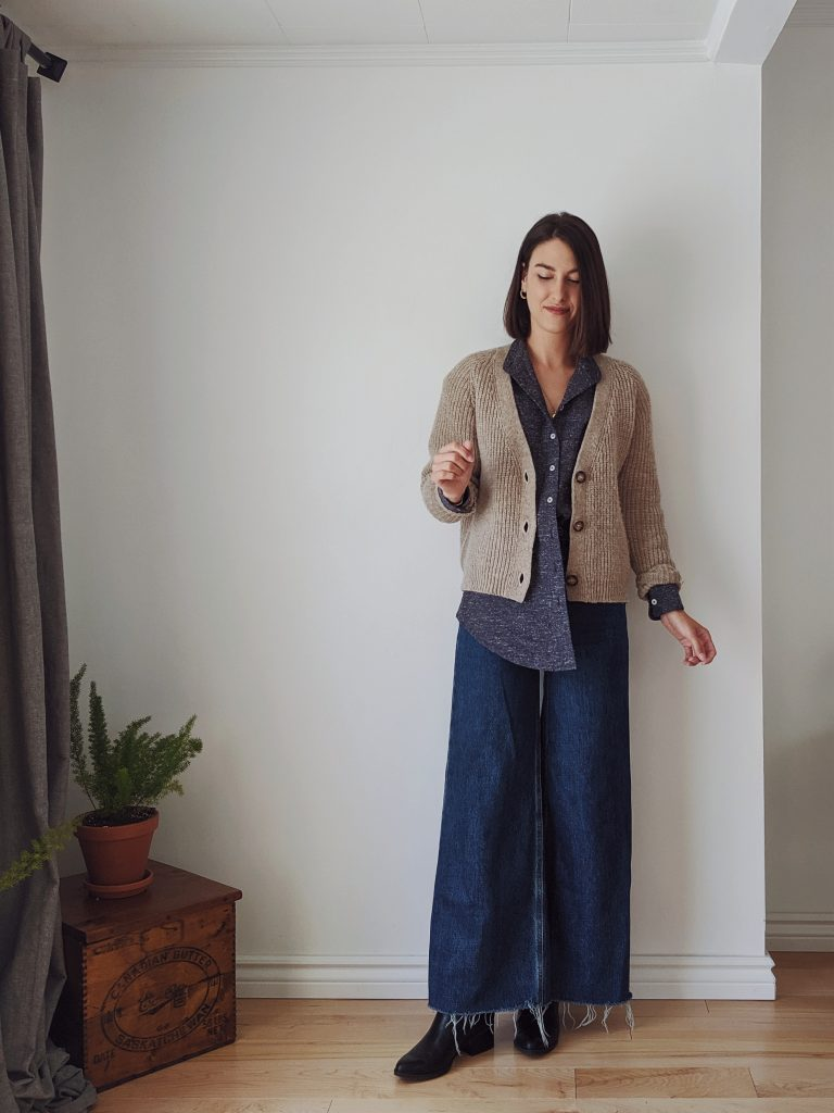 Woman with a brown bob standing against a white wall wearing wide leg dark blue jeans, a half-tucked textured blue button-up and a classic natural knit cardigan