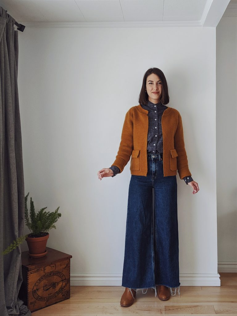 Woman with a brown bob standing against a white wall wearing indigo wide leg jeans with a dark blue textured button-up tucked in. She's wearing cognac mules that match with a vintage pumpkin-coloured, structured cardigan