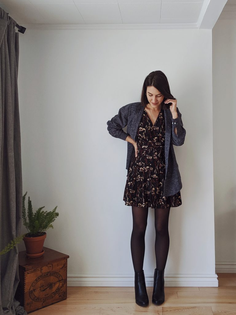 Woman with a brown bob standing against a white wall wearing a short dark floral dress with sheer black tights, black booties and a dark blue textured button-up as a chore coat
