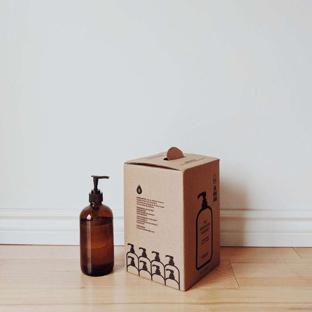 An amber bottle of hand soap stands against a white wall beside a cardboard box that contains refill soap and graphic design elements in black ink.