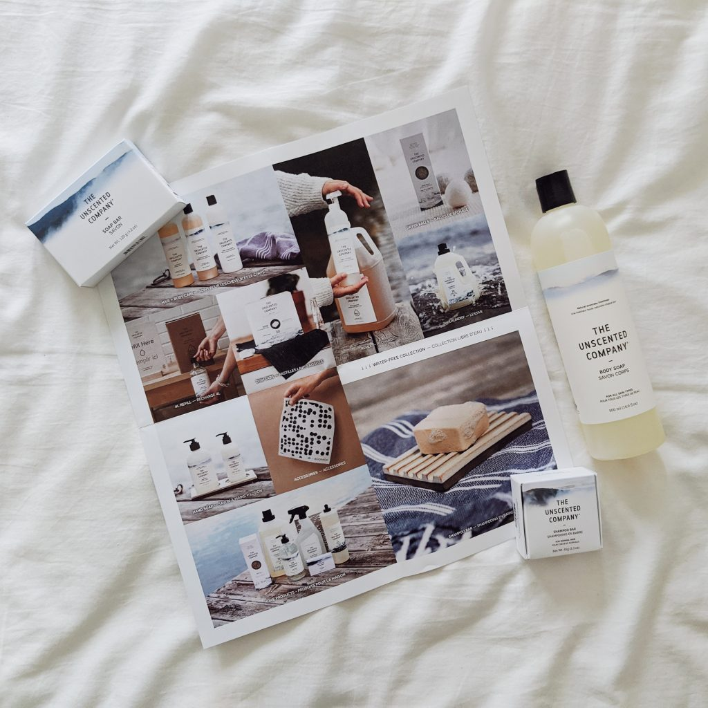 A gathering of Unscented Co. products with an opened brand booklet that features various photos of their products in nature.