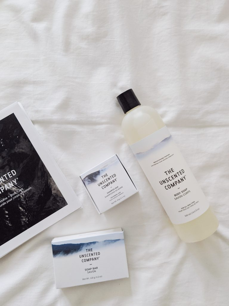 A gathering of Unscented Co. products on a white sheet, with a closed brand booklet.