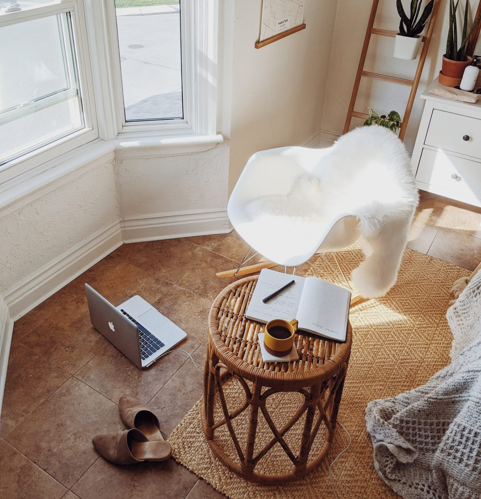 A macbook laptop sitting on the floor of a room with a white eames rocker chair and rattan stool, which has a coffee mug and notebook on it. Shoes lay strewn to the side of the frame.