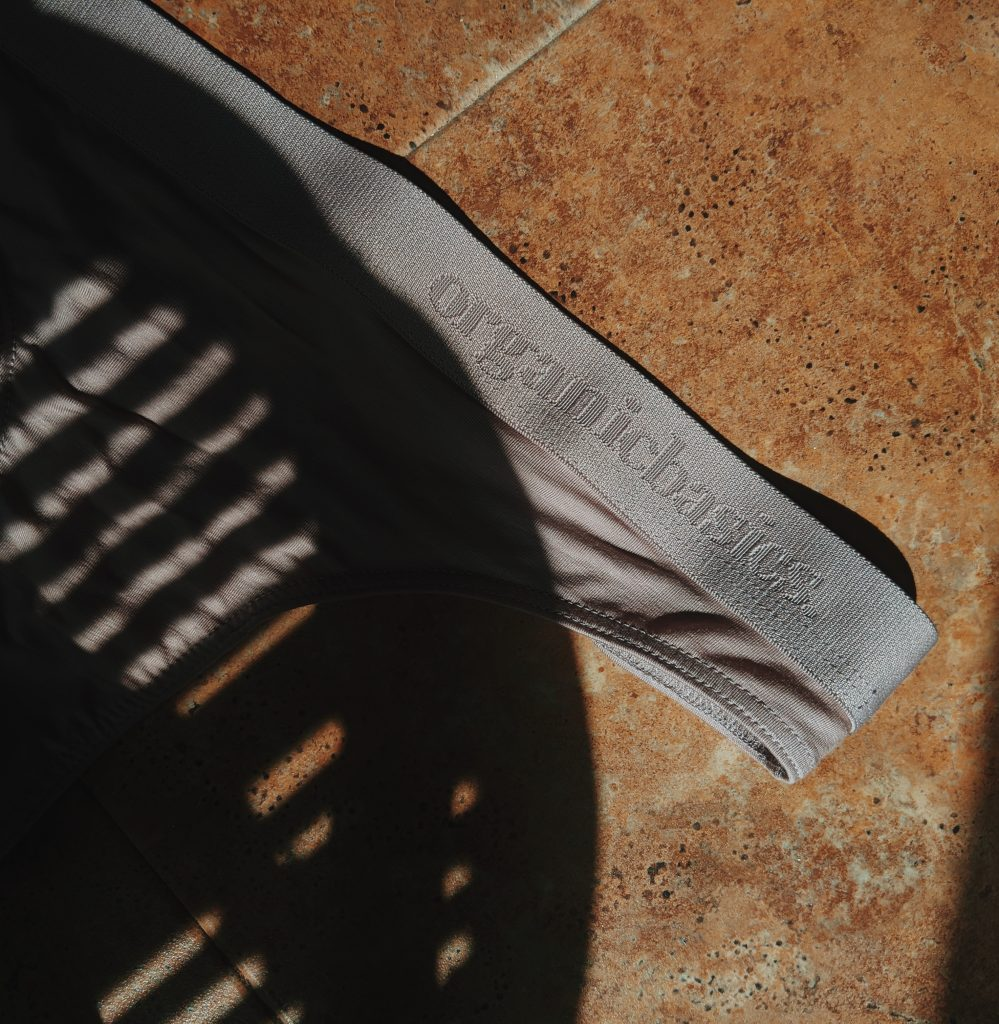 A moody shot of the Organic Basics elastic band on their underwear, partially shaded and in intense warm sunlight