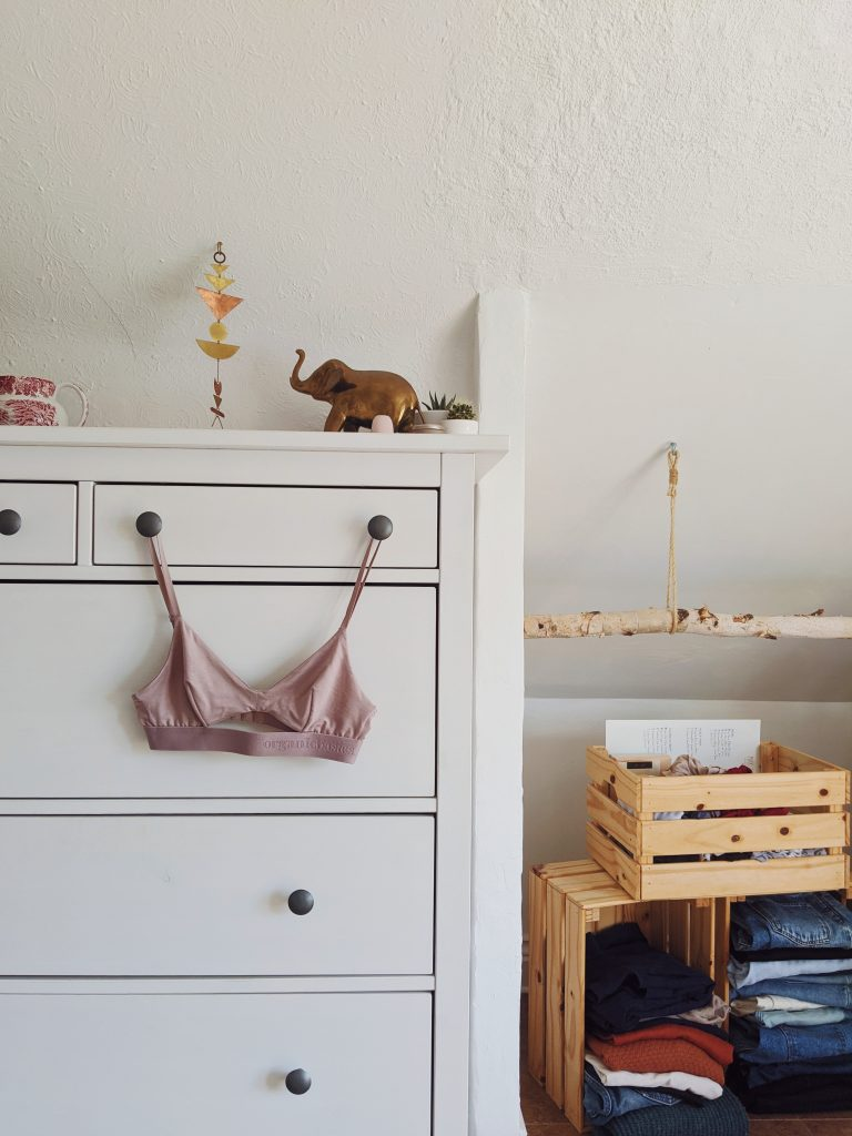The Organic Basics triangle bralette dangling from the knobs of a white Ikea dresser. you can see stacked crates in an open closet on the right hand side, with folded clothes inside them.